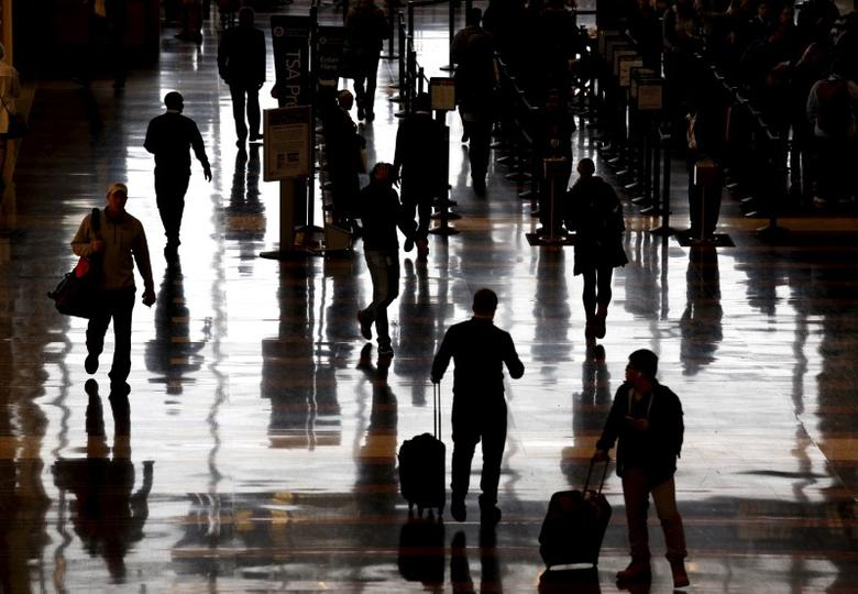 Travelers make their way through Reagan National Airport in Washington December 23, 2015. Unseasonably warm and rainy weather has created foggy conditions have created travel delays to many cities along the East Coast.  REUTERS/Kevin Lamarque