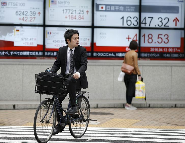 A man cycles in front of an electronic board showing Japan's Nikkei average (R) outside a brokerage in Tokyo, Japan, April 13, 2016.   REUTERS/Toru Hanai - RTX29P5O