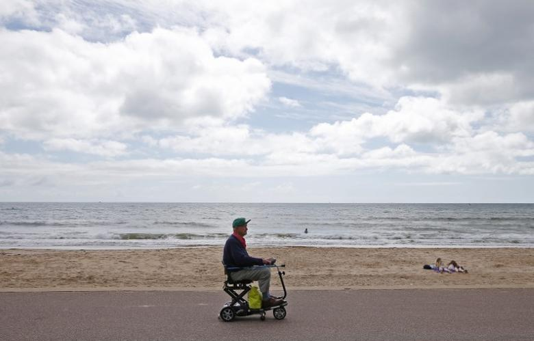 A man rides his mobility scooter near the beach in Bournemouth, Britain August 6, 2015. REUTERS/Eddie Keogh