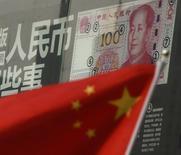 Una bandera china frente a un billete de 100 yuanes, en una sucursal de un banco en un distrito comercial en Pekín, China. 21 de agosto de 2016. La inversión china en activos fijos aumentó un 8,2 por ciento entre enero y septiembre respecto mismo lapso del año anterior, en línea con las expectativas del mercado, luego de que el Gobierno intensificó el gasto en infraestructura para apoyar a la economía. REUTERS/Kim Kyung-Hoon
