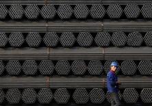 Un trabajador caminando junto a pilas de productos de acero en una planta en Tangshan, China. 3 de noviembre de 2015. La producción de acero crudo de China creció un 3,9 por ciento en septiembre frente al mismo mes del año previo, mostraron datos del Gobierno el miércoles. REUTERS/Kim Kyung-Hoon/File Photo