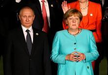 Президент России Владимир Путин и канцлер Германии Ангела Меркель на саммите G20 в Ханчжоу, Китай, 4 сентября 2016 года. Введение санкций в отношении России за роль в сирийской войне остается в повестке Запада, но решения вряд ли будут приняты на саммите ЕС на этой неделе, сообщил в среду высокопоставленный чиновник правительства Германии. REUTERS/Damir Sagolj