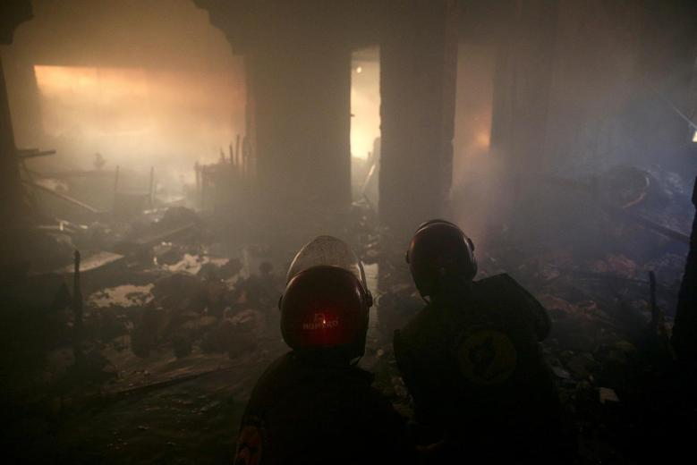 Civil Defence members walk through smoke as they try to put out a fire inside a building after shelling in the rebel held besieged town of Douma, eastern Ghouta in Damascus, Syria October 19, 2016. REUTERS/Bassam Khabieh