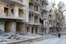 El Ejército sirio dijo este jueves que el alto al fuego unilateral apoyado por Rusia había entrado en vigor para permitir a la gente abandonar la parte oriental de Alepo , que está bajo asedio, un movimiento que según los rebeldes forma parte de una campaña psicológica para hacerles rendirse. En la imagen, un hombre camina junto a edificios dañados en el vecindario al-Sukkari, tomado por fuerzas rebeldes, en Alepo, el 19 de octubre de 2016. REUTERS/Abdalrhman Ismail