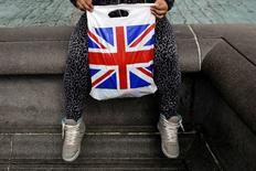 Las ventas minoristas británicas registraron su mejor trimestre desde finales de 2014 en los tres meses hasta septiembre, pero las cálidas temperaturas y los precios más altos redujeron la demanda de ropa nueva hacia el final del periodo. En la imagen, una mujer con una bolsa ilustrada con la bandera británica en Londres, el 23 de abril de 2016.  REUTERS/Kevin Coombs