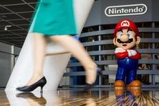 Женщина проходит мимо фигурки Марио в центре Nintendo в Токио 29 июля 2015 года. Nintendo Co Ltd представила новую игровую консоль Nintendo Switch, пытаясь догнать главных конкурентов на рынке видеоразвлечений - Sony Corp и Microsoft Corp. REUTERS/Thomas Peter