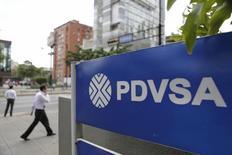 Una persona camina cerca del logo de PDVSA en una gasolinera en Caracas. La estatal Petróleos de Venezuela quiere recibir ofertas de adquisición por 600 millones de dólares adicionales en un canje de su deuda, de preferencia de los bonos que vencen en noviembre de 2017, a fin de llegar a los niveles de participación que requiere, dijo el viernes una fuente cercana a la operación. REUTERS/Marco Bello