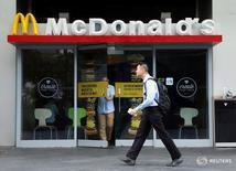 Мужчина проходит мимо ресторана McDonald's в Сингапуре 25 июля 2016 года.  McDonald's Corp. активизировал процесс реструктуризации в прошлом квартале, и рост продаж превзошел ожидания аналитиков, отправив акции компании вверх более чем на 2 процента. REUTERS/Edgar Su/File Photo
