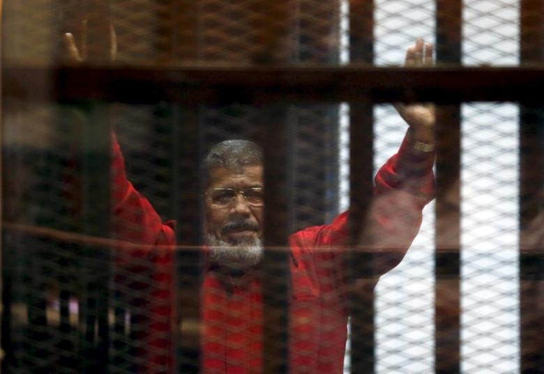 FILE PHOTO: Deposed President Mohamed Mursi greets his lawyers and people from behind bars at a court wearing the red uniform of a prisoner sentenced to death, during his court appearance with Muslim Brotherhood members on the outskirts of Cairo, Egypt, June 21, 2015.  REUTERS/Amr Abdallah Dalsh/File photo