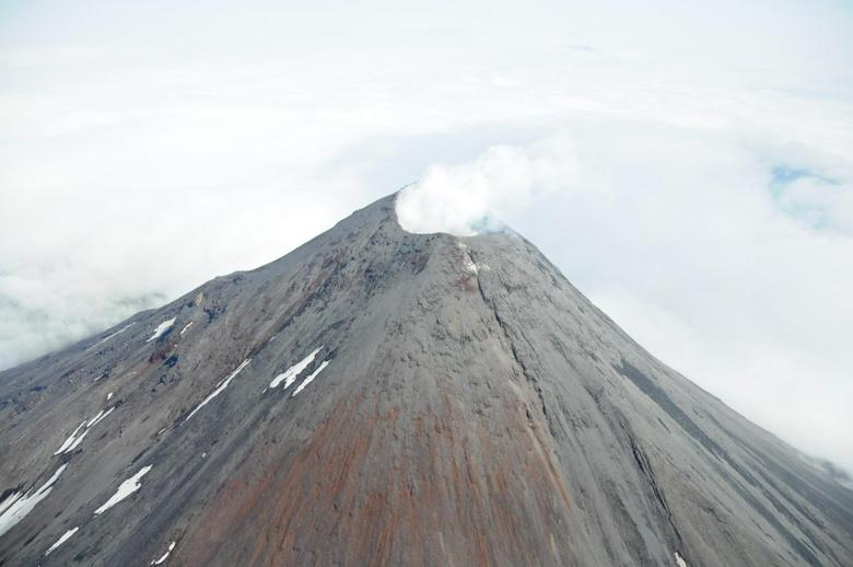 An aerial photograph shows the Cleveland Volcano during the time a small lava flow, or dome, was accumulating in the summit crater as the 660 foot wide summit crater emits a white, largely steam condensate cloud in this August 8, 2011 file photo. REUTERS/Kym Yano, National Oceanic and Atmospheric Administration/Handout File Photo
