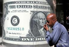 Мужчина проходит мимо пункта обмена валюты в Каире 13 октября 2016 года. Поддерживаемый ожиданиями роста ставок ФРС США в конце года, доллар удерживал позиции в часы ранних торгов в Азии, находясь немного ниже пика девяти месяцев, установленного накануне; австралийский доллар укрепил позиции, поскольку из-за данных инфляции вероятность снижения ставки в Австралии уменьшилась. REUTERS/Mohamed Abd El Ghany