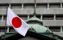 Японский флаг над зданием Банка Японии в Токио. Банк Японии, скорее всего, воздержится от расширения мер стимулирования на следующей неделе, несмотря на ожидаемое ухудшение ценового прогноза, которое может указать на то, что инфляция не достигнет 2-процентного целевого уровня до окончания срока пребывания на посту главы регулятора Харухико Куроды. REUTERS/Toru Hanai