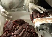 Un trabajador en un frigorífico de carnes en Sao Paulo, sep 9, 2005. La firma brasileña JBS SA, la mayor exportadora mundial de carne bovina, dijo el miércoles que canceló un plan de reorganización corporativa debido a la oposición de uno de sus principales accionistas, el gubernamental banco de inversión BNDES.    REUTERS/Paulo Whitaker (BRAZIL)