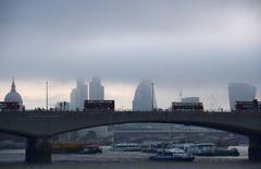 """Trabajadores cruzan el río Támesis con el distrito financiero de la City de Londres de fondo. 27 octubre 2016. La economía de Reino Unido se desaceleró levemente en los tres meses posteriores a la votación del """"Brexit"""", indicaron datos oficiales el jueves, desafiando las advertencias de un duro impacto y disminuyendo más las posibilidades de un recorte de las tasas interés del Banco de Inglaterra la próxima semana. REUTERS/Toby Melville"""