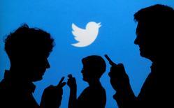 Varias personas miran sus móviles con el logo de Twitter de fondo. 27 septiembre de 2013. El crecimiento de los ingresos de Twitter Inc se ralentizó de forma abrupta en el tercer trimestre, aunque superó las previsiones de los analistas, y la compañía anunció que reducirá en un 9 por ciento su fuerza laboral global. REUTERS/Kacper Pempel