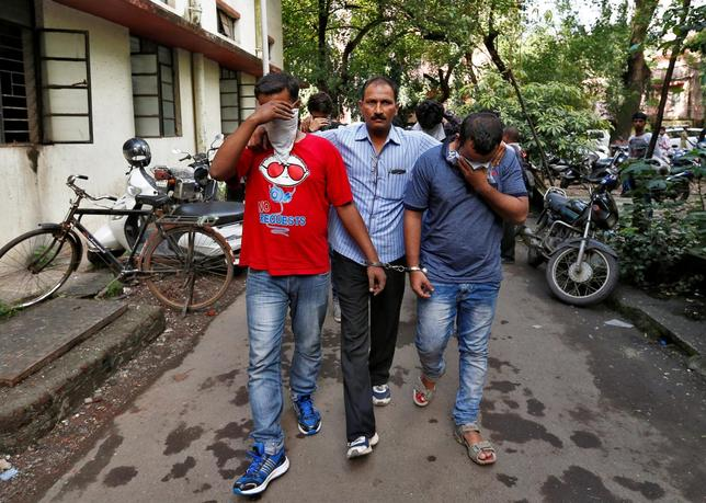 A policeman escorts men who they said were arrested on Wednesday on suspicion of tricking American citizens into sending them money by posing as U.S. tax officials, at a court in Thane, on the outskirts of Mumbai, India, October 6, 2016. REUTERS/Danish Siddiqui