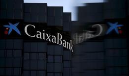 Caixabank anunció el viernes un incremento del beneficio neto del 15,3 por ciento en el tercer trimestre en comparación con el mismo periodo de un año antes, aunque en la comparación con el trimestre anterior bajó un 9,1 por ciento en un entorno de tipos de interés en tipos mínimos que lastra la rentabilidad en el sector. En la imagen de archivo, el logo de CaixaBank reflejado en un cristal en la sede de la empresa en Barcelona,. REUTERS/Albert Gea/File Photo