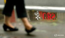 Логотип швейцарского банка UBS отражается в луже в Цюрихе 30 июля 2013 года. Швейцарский банк UBS подтвердил нерадостный прогноз рыночных условий после крутого падения чистой прибыли и увеличения отчислений на судебные издержки, связанные с нарушениями во время продажи обеспеченных ипотечными кредитами бумаг. REUTERS/Arnd Wiegmann/File Photo