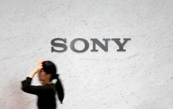 Sony recortó su pronóstico de beneficios anuales debido a las pérdidas relacionadas con la venta de su negocio de baterías, lo que decepcionó a un mercado que había previsto una revisión al alza por las sólidas ventas de su consola PlayStation 4 y el lanzamiento de su casco de realidad virtual. En la imagen de archivo, una recepcionista camina junto a un logo de Sony en su sede de Tokio. REUTERS/Yuya Shino/File Photo