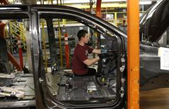 A Fiat Chrysler assembly worker works on the interior of a partially assembled minivans at the Windsor Assembly Plant in Windsor, Ontario, February 9, 2015. REUTERS/Rebecca Cook