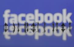 Las acciones de Facebook se derrumbaron más de un 6 por ciento el miércoles en operaciones tras el cierre después de que la compañía advirtiera de que el crecimiento de sus ingresos podría desacelerarse, contrarrestando unas sólidas alzas de beneficio que habían superado cómodamente las estimaciones de Wall Street. En la imagen de archivo, figuras de personas frente a un logo de Facebook en una fotoilustración. REUTERS/Dado Ruvic/Illustration