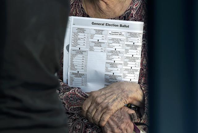 A woman carries her sample ballot before she casts her ballot during voting in the 2016 presidential election at Desert Pines High School in Las Vegas, Nevada, U.S November 8, 2016.  REUTERS/David Becker