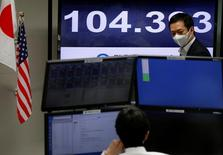 Японские валютные трейдеры у мониторов с курсом доллара к иене в Токио 8 ноября 2016 года. Американский доллар упал на 0,5 процента к иене в начале торгов в Азии в среду из-за озабоченности рынков выборами президента в Америке, где не закончился вторник и начали поступать первые данные об итогах голосования. REUTERS/Toru Hanai