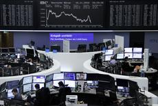 Traders work at their desks in front of the German share price index, DAX board, at the stock exchange in Frankfurt, Germany, November 10, 2016. REUTERS/Staff/Remote