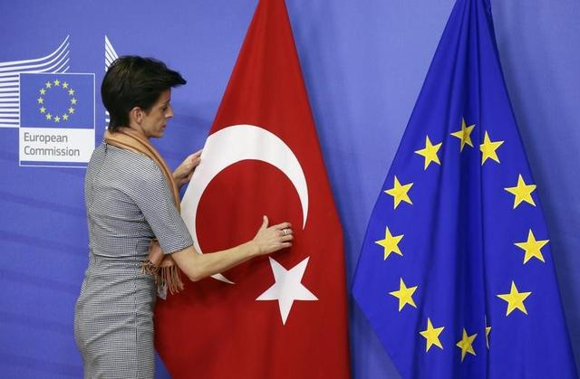 A woman adjusts the Turkish flag next to the European Union flag before the arrival of Turkish Prime Minister Ahmet Davutoglu (unseen) at the EU Commission headquarters in Brussels January 15, 2015. REUTERS/Francois Lenoir