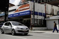 Un auto y un transehúnete pasan frente a un comercio de Bridgestone Firestone en Caracas, Venezuela, Nov 5, 2016. Después de casi 50 años de operar en Venezuela, en enero del 2015 la autopartista estadounidense Dana vendió sus fábricas en el centro del país a un grupo local, luego de que el ensamblaje de autos colapsara bajo el peso de la deprimida economía local. REUTERS/Marco Bello