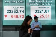 Люди рядом с экранами, демонстрирующими данные об индексе Hang Seng. Фондовый рынок Китая завершил торги среды практически без изменений, при этом акции сырьевых тяжеловесов сдали позиции на фоне опасений, что резкое падение на фьючерсном товарном рынке страны может заставить регуляторов ужесточить ограничения для ослабления волатильности. REUTERS/Tyrone Siu