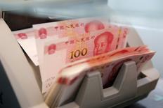 En la imagen de archivo, una máquina cuenta billetes de 100 yuanes chinos en la filial de un banco comercial en Pekín. 30 de marzo de 2016. El yuan chino se debilitó el miércoles a un mínimo de ocho años, luego de que las expectativas de unas tasas de interés más altas en Estados Unidos impulsaron al dólar, y en momentos en que Donald Trump se prepara para asumir el cargo de presidente de ese país.REUTERS/Kim Kyung-Hoon