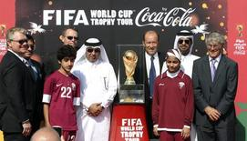 Qatar Football Association general secretary Saoud Al-Mohannadi (5th L), FIFA representative Gabriel Calderon of Argentina (4th R) and soccer coach Bora Milutinovic (R) pose with others next to the FIFA World Cup trophy following its arrival in Doha, on a tour, December 12, 2013.  REUTERS/Fadi Al-Assaad