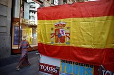 La deuda del conjunto de las Administraciones Públicas españolas subió en unos 2.800 millones de euros en septiembre, hasta los 1,105 billones de euros, manteniéndose por encima del 100 por cien del Producto Interior Bruto (PIB), según datos del Banco de España. En la imagen de archivo, una mujer pasa junto a una bandera española, el 24 de agosto de 2016. REUTERS/Andrea Comas