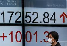 En la imagen, un hombre pasa frente a un panel electrónico de una casa de bolsa en Tokio, Japón. 10 de noviembre de 2016. El índice Nikkei de la bolsa de Tokio subió levemente el jueves luego de que la primera operación de compra de deuda a tasa fija del Banco de Japón debilitó el yen. REUTERS/Toru Hanai
