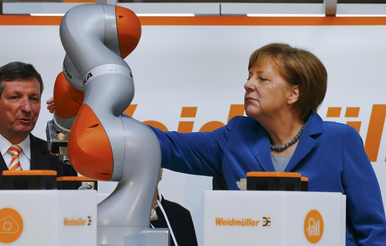 German Chancellor Angela Merkel watches the work of KUKA robot during the opening tour at the Hannover Messe in Hanover, Germany April 25, 2016. REUTERS/Wolfgang Rattay/File Photo