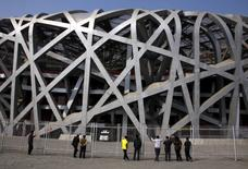 """Chinese tourists look through a security fence at the National Stadium, also known as the """"Bird's Nest"""", which was the venue for the athletics and the opening and closing ceremonies of the 2008 Olympic Games in Beijing March 23, 2012.  Picture taken March 23, 2012. REUTERS/David Gray"""