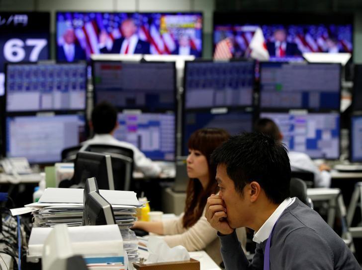 2016年11月9日,日本一家外汇交易公司雇员在工作中,附近电视画面是美国当选总统特朗普在讲话。REUTERS/Toru Hanai