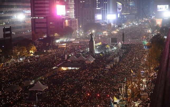 11月21日、韓国の主要野党が朴槿恵大統領の弾劾準備に動き始める。「国民の党」は大統領の弾劾動議に必要な署名を集めるため、他の政党との協議を開始すると発表。写真はろうそくを手に朴大統領の辞任を求める群衆。ソウル市内中心部で19日撮影(2016年 ロイター/Jung Yeon-Je)