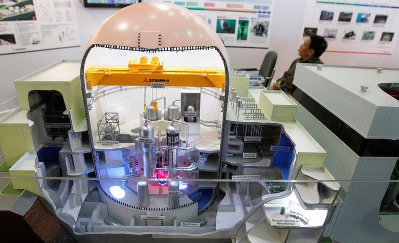 A man sits behind a model of a Japanese Mitsubishi nuclear reactor at the World Nuclear Power 2012 exhibition in Hanoi, Vietnam October 26, 2012.    REUTERS/Kham/File Photo