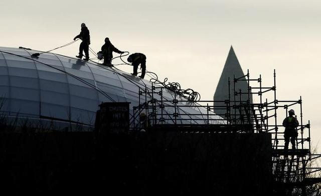 With the Washington Monument looming in the background, a crew works on the roof of the newly constructed United States Institute of Peace in Washington January 21, 2010.   REUTERS/Kevin Lamarque