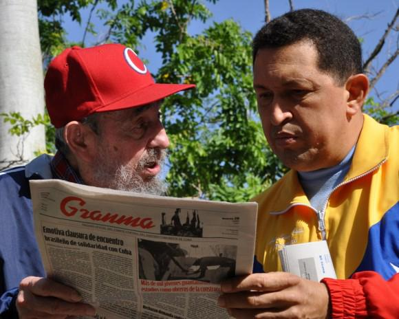 Former Cuban leader Fidel Castro and Venezuela's former President Hugo Chavez read a copy of the Cuban Communist Party (PCC) newspaper ''Granma'' in Havana June 28, 2011, in this handout picture. REUTERS/Revolution Studios/Cubadebate