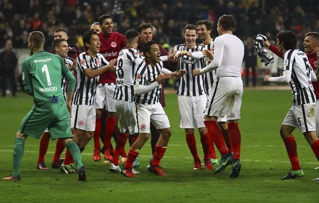 11月26日、サッカーのドイツ1部ブンデスリーガ、アイントラハト・フランクフルトはドルトムントを2─1で下した。写真は勝利を喜ぶフランクフルトの選手たち(2016年 ロイター/Kai Pfaffenbach)
