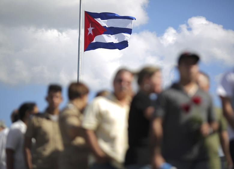 A Cuban flag flies overhead as people wait in line to pay tribute to Cuba's late President Fidel Castro in Havana, Cuba, November 28, 2016.  REUTERS/Carlos Barria