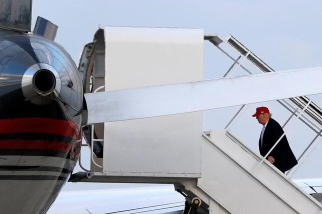 11月28日、トランプ氏は米キューバ間の取引中止もあり得るとの考えを示唆した。写真はフロリダ州で飛行機に乗り込む同氏。27日撮影(2016年 ロイター/Joe Skipper)