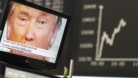 Телеэкран с изображением избранного президента США Дональда Трампа на фоне табло с динамикой индекса немецкого фондового рынка DAX на бирже во Франкфурте 9 ноября 2016 года. Международное рейтинговое агентство Fitch во вторник предупредило о нарастании политического риска для суверенных заемщиков по всему миру из-за последствий решения британцев покинуть ЕС, а американцев - избрать президентом Дональда Трампа. REUTERS/Kai Pfaffenbach