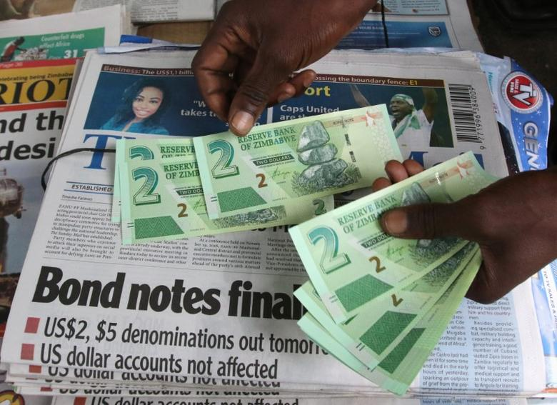 A street vendor poses with new bond notes in the capital Harare, Zimbabwe, November 28, 2016. REUTERS/Philimon Bulawayo