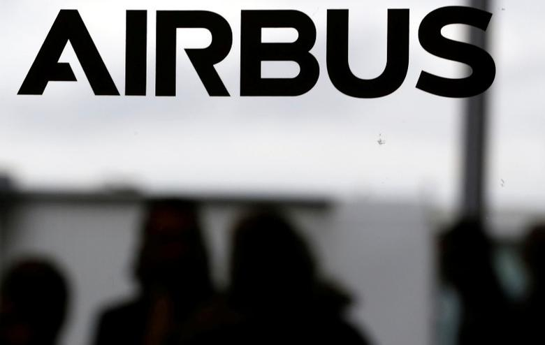 People are seen in silhouette behind the logo of Airbus during the Airbus A350-1000 maiden flight event in Colomiers near Toulouse, Southwestern France, November 24, 2016.  REUTERS/ Regis Duvignau
