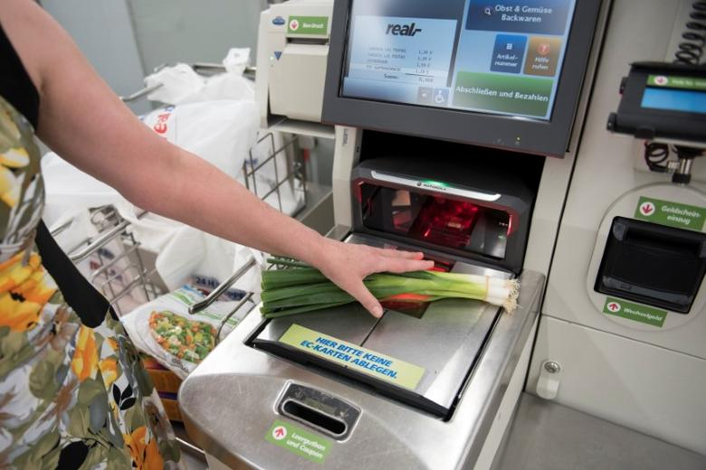 A customer weighs vegetable at a self service point of sale terminal in a store in Berlin, Germany August 26, 2016. REUTERS/Stefanie Loos