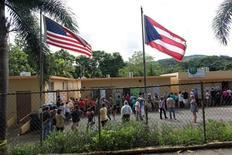"""Люди перед зданием школы, где располагется участок для голосования на выборах губернатора. Гуайнабо, Пуэрто-Рико, 8 ноября 2016 года. Пуэрто-Рико, страдающий от затяжной """"депрессии"""", уже начал экономическое восстановление, которое может скопировать рост таких американских городов, как Нью-Йорк, если остров продолжит уделять внимание бюджетно-налоговой ситуации и трудоустройству, сказал чиновник ФРС во вторник. REUTERS/Alvin Baez"""